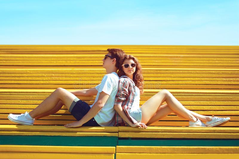 Fashion young couple teenagers resting in the city park sitting on the bench royalty free stock photo