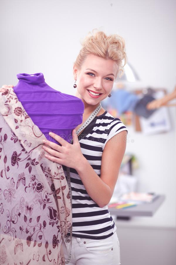 Fashion young designer woman standing near mannequin royalty free stock images
