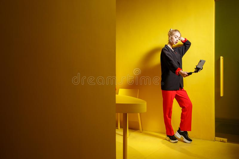 Fashion young girl blogger dressed in red trousers and black jacket takes a selfie on her smartphone in the room with stock photo