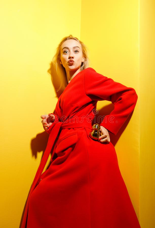 Fashion young girl blogger dressed in stylish red coat poses with the gold little duck figurine in her hands on the royalty free stock image
