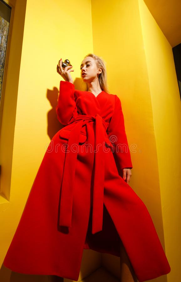 Fashion young girl blogger dressed in stylish red coat poses with the gold little duck figurine in her hands on the royalty free stock photos