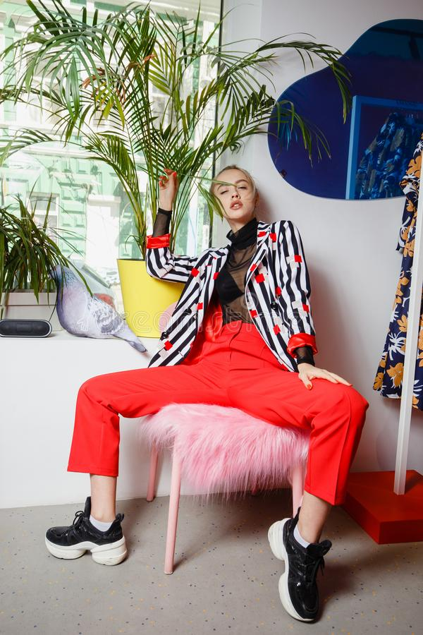 Fashion young girl blogger dressed in stylish striped jacket and red trousers poses sitting on the stool with pink fur stock images