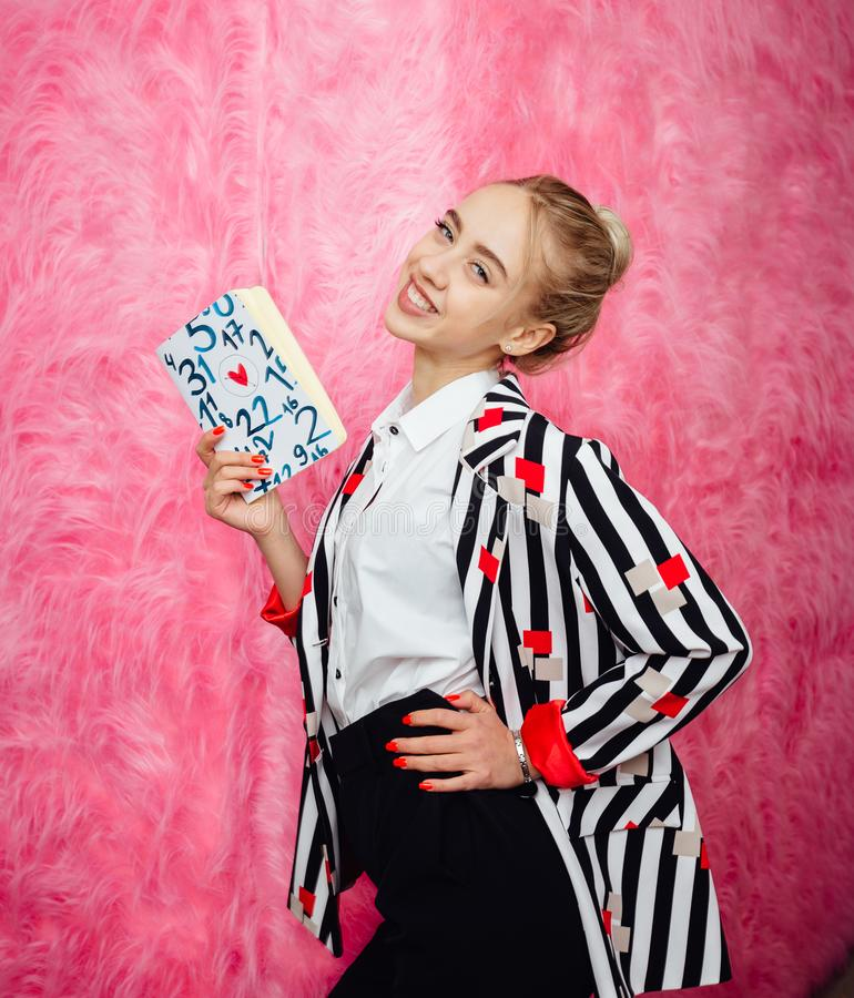 Fashion young girl blogger dressed in stylish striped shirt and red trousers poses on the background of pink fur wall stock photos