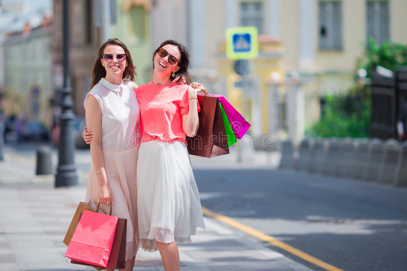 Fashion young girls with shopping bags walking along city street. Sale, consumerism and people concept. royalty free stock photography