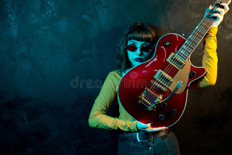 Fashion young hipster woman with curly hair with red guitar in neon lights. Rock musician is playing electrical guitar. 90s style concept stock photography