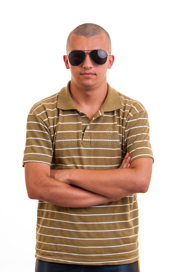 Fashion young man with sunglasses. Fashion young man holding sunglasses with a serious look and hands cross stock photos