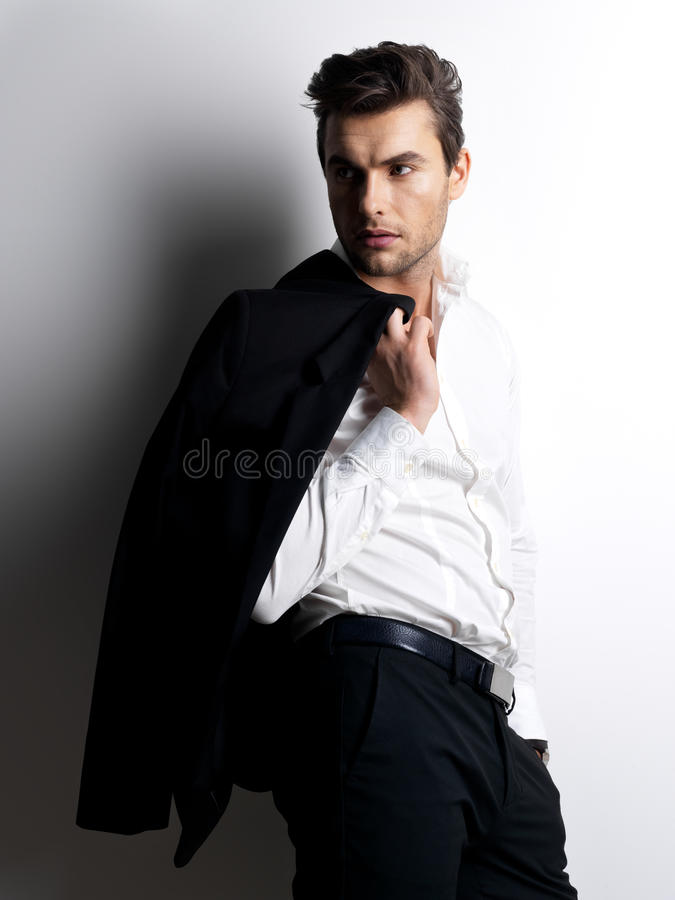 Fashion young man in white shirt holds the black jacket. Over wall with contrast shadows royalty free stock image