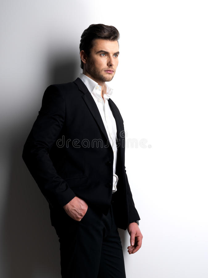 Fashion young man in white shirt holds the black jacket. Profile portrait of a Fashion young man in black suit posing at studio stock images