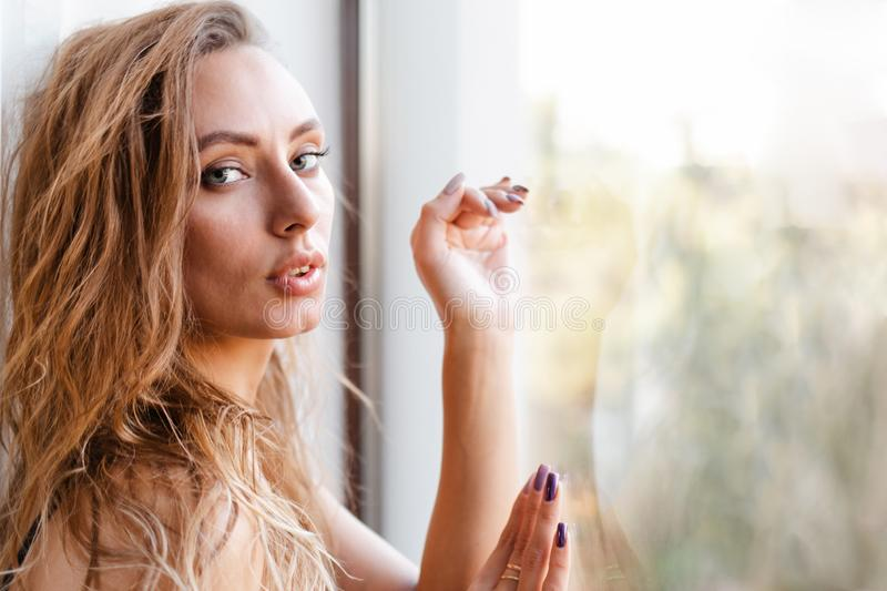 Fashion. A young slender blonde Woman in black clothes, posing leaning on the window glass. Copy space stock photography