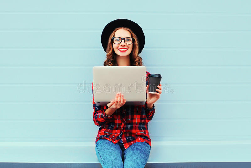 Fashion young smiling woman holding laptop computer with coffee cup resting outdoors in city, wearing black hat red checkered stock photography