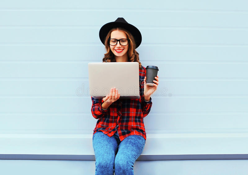 Fashion young smiling woman using laptop computer with coffee cup resting outdoors in city, wearing black hat red checkered shirt royalty free stock images