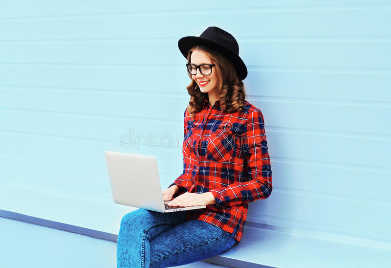 Fashion young smiling woman working using laptop computer outdoors in city, wearing a black hat, red checkered shirt. Fashion young smiling woman working using royalty free stock image