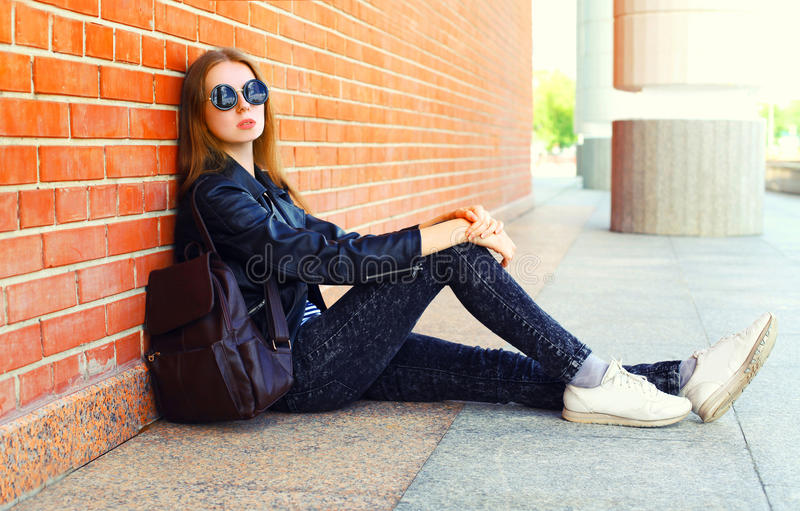 Fashion young woman in black rock style sitting over background stock photography