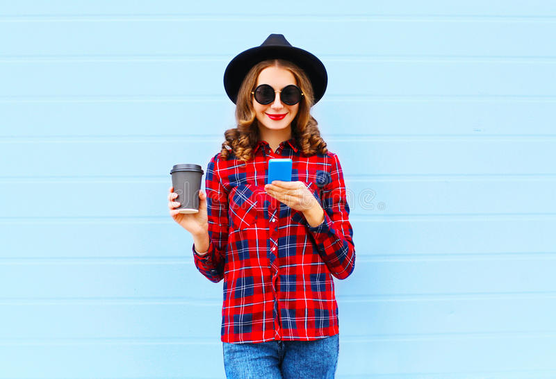 Fashion young woman with coffee cup resting using smartphone outdoors in city, wearing black hat red checkered shirt. Fashion young woman with coffee cup resting royalty free stock images