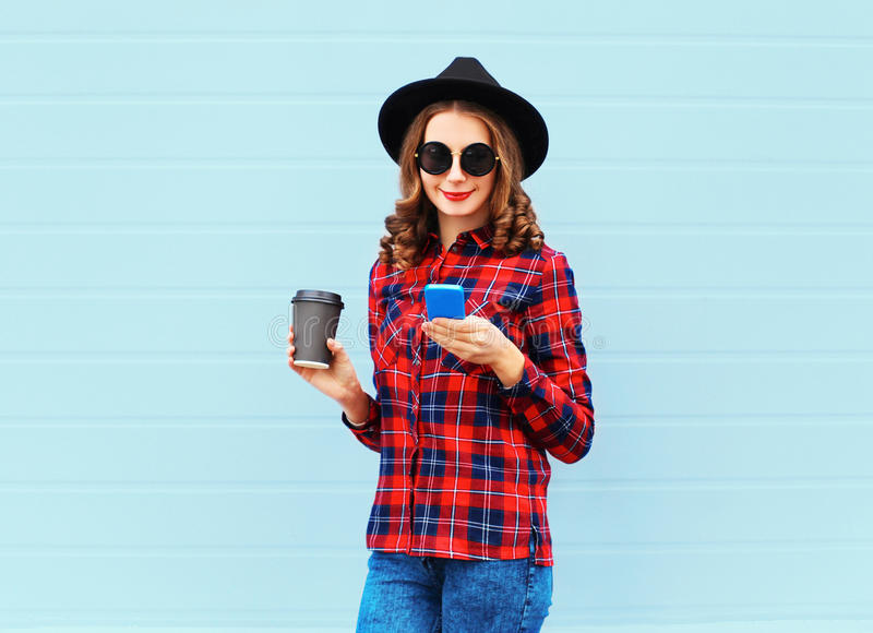 Fashion young woman with coffee cup resting using smartphone outdoors in city, wearing a black hat red checkered shirt. Fashion young woman with coffee cup stock photography