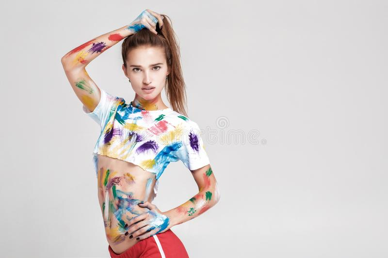 Young woman smeared in multicolored paint. royalty free stock images