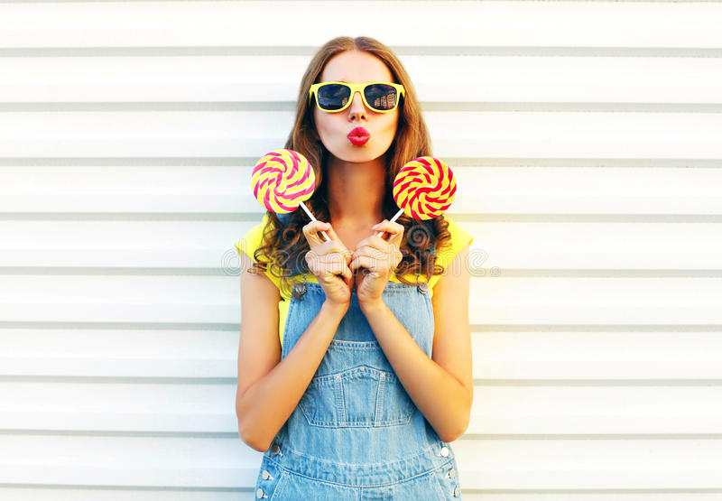 Fashion young woman holding a lollipops and blowing her lips royalty free stock photos