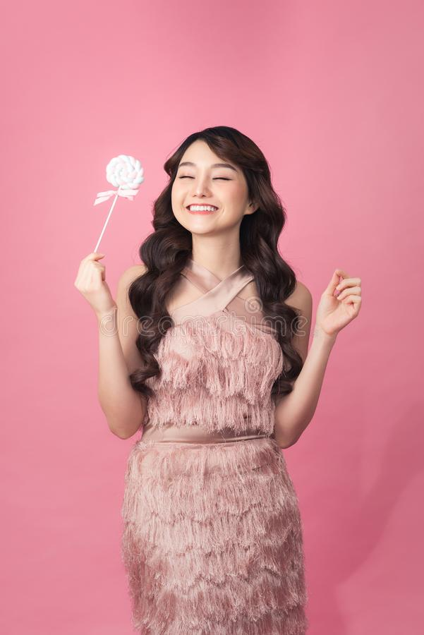 Fashion young woman with sweet makeup holding lolipop in her hands royalty free stock images