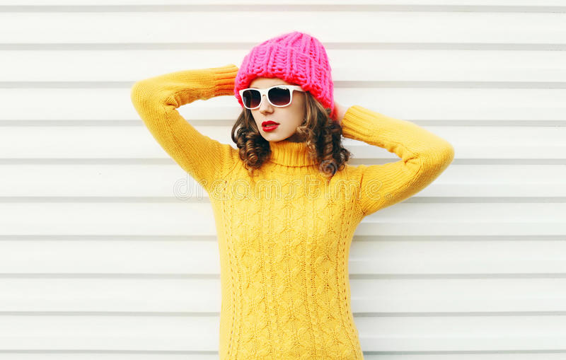 Fashion young woman wearing a knitted pink hat, yellow colorful sweater over white. Background royalty free stock images