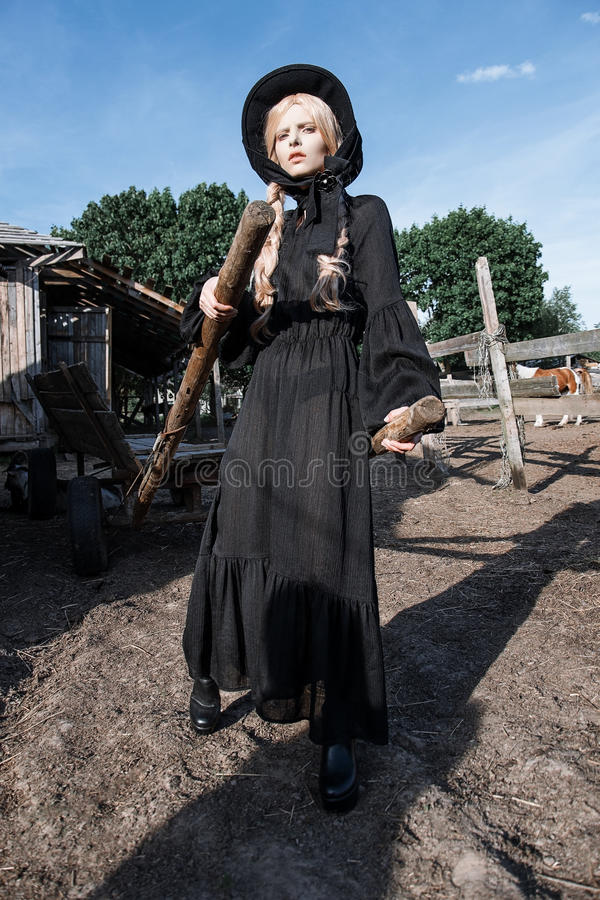 Fashion young woman wearing stylish black dress and hat at countryside. Amish fashion style. royalty free stock photos
