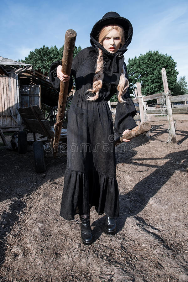 Fashion young woman wearing stylish black dress and hat at countryside. Amish fashion style. stock images