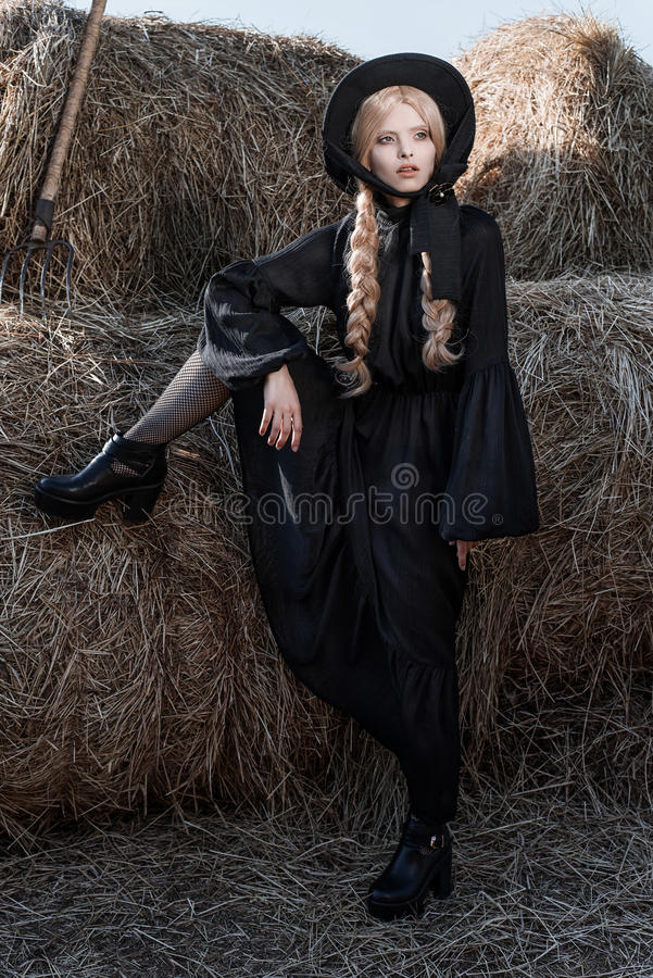 Fashion young woman wearing stylish black dress and hat at countryside. Amish fashion style. stock photography