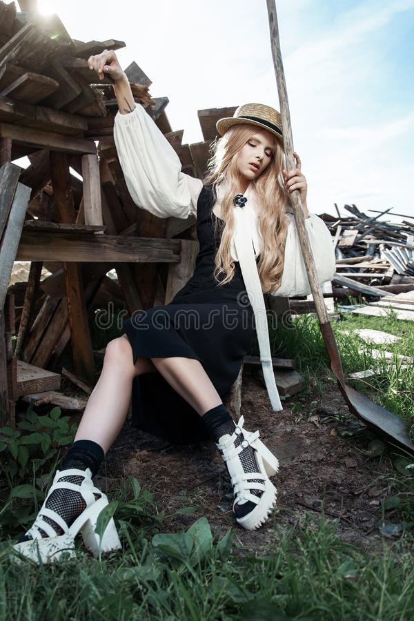 Fashion young woman wearing stylish dress and straw hat at countryside. Amish fashion style. stock photos