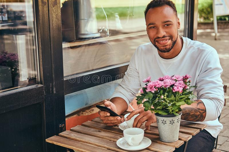 A fashionable African-American bearded male sitting near a coffee shop with a cup of coffee, using a smartphone. stock photo