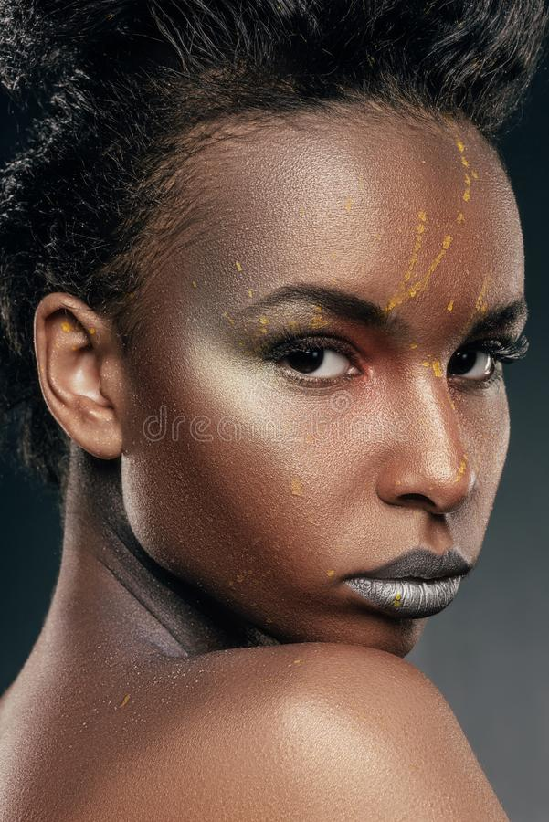 Fashionable african american girl. With silver makeup and yellow powder on face stock photo