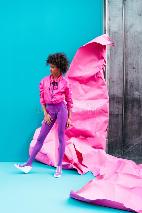 Fashionable african american girl posing in 80s style clothes on turquoise. With pink paper royalty free stock image