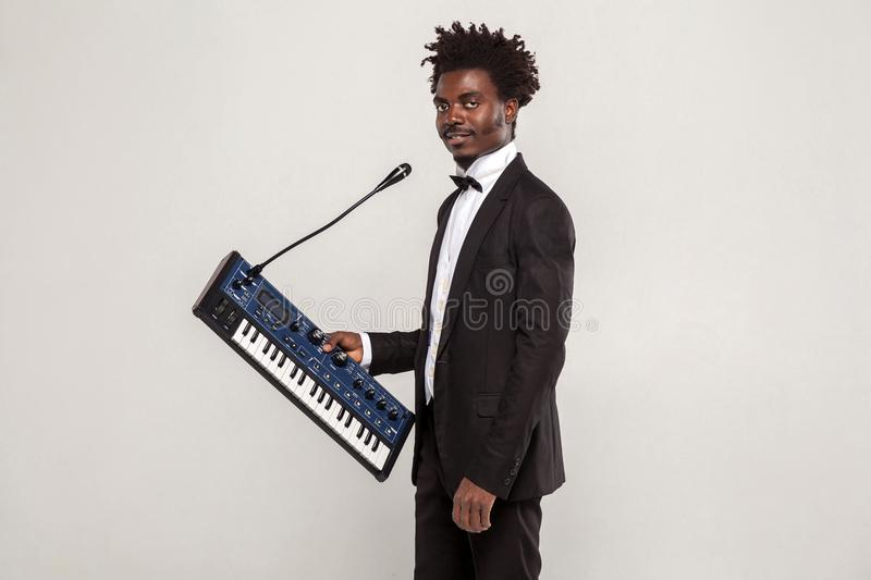 Fashionable african singer holding synthesizer ,looking at camera stock photography