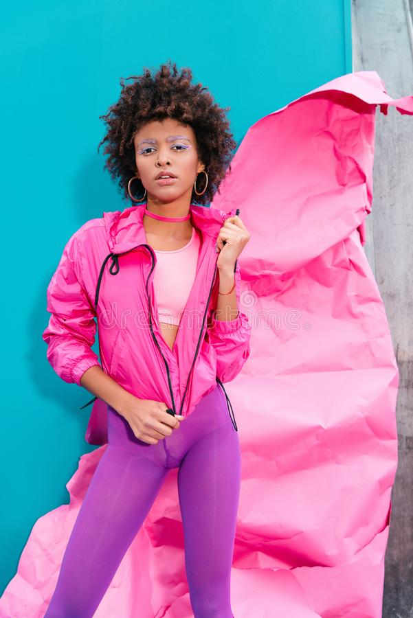 Fashionable afro model posing in 80s style clothes on turquoise. With pink paper royalty free stock photography