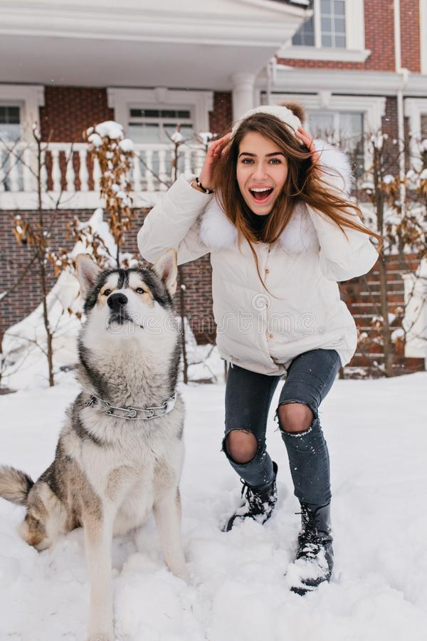 Fashionable amazing girl having fun with cute husky dog outdoor in snow. Happy winter time of real friends, home pets royalty free stock photo