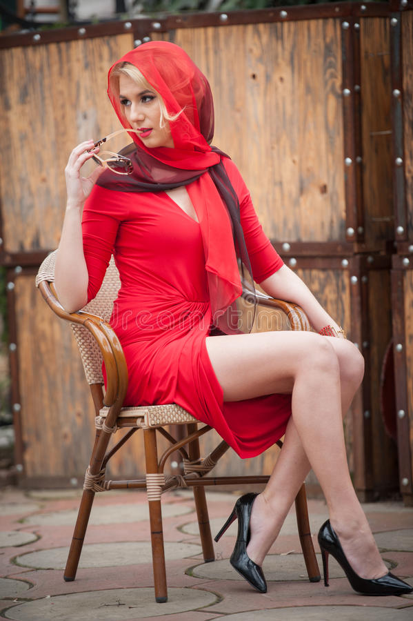 Fashionable attractive blonde woman in red dress sitting on chair. Beautiful elegant woman with red scarf posing in elegant scene royalty free stock photo