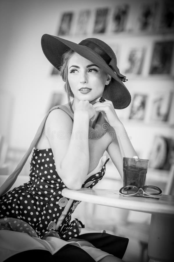 Fashionable attractive lady with hat and scarf sitting in restaurant, indoor shot. Young woman posing in elegant scenery stock images