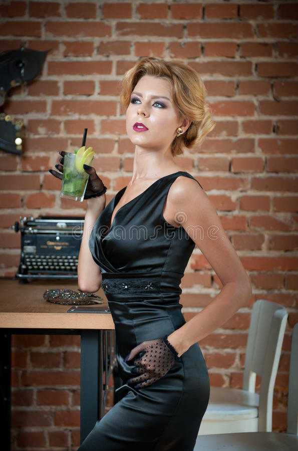 Fashionable attractive lady with little black dress and gloves standing near a table in restaurant holding a glass of drink. Short hair blonde woman with stock images