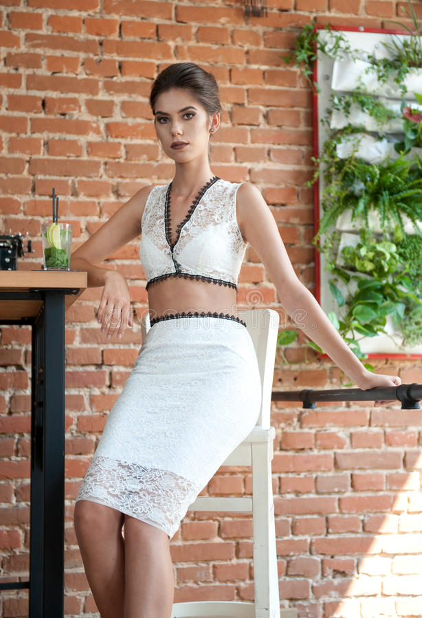 Fashionable attractive lady with white dress standing near a restaurant table having a drink. Short hair brunette woman royalty free stock photo