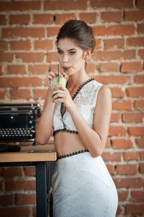 Fashionable attractive lady with white dress standing near a restaurant table having a drink. Short hair brunette woman royalty free stock images