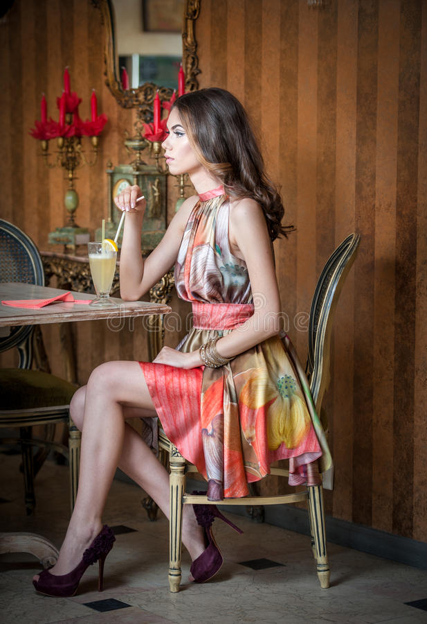 Fashionable attractive woman in multicolored dress sitting in restaurant. Beautiful brunette posing in elegant vintage scenery royalty free stock images