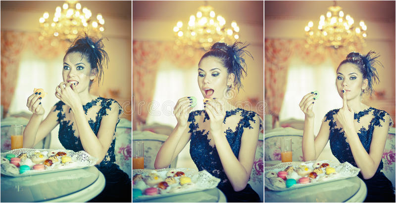 Fashionable attractive young woman in black dress eating macaroons in restaurant. Beautiful brunette holding cookies stock photos