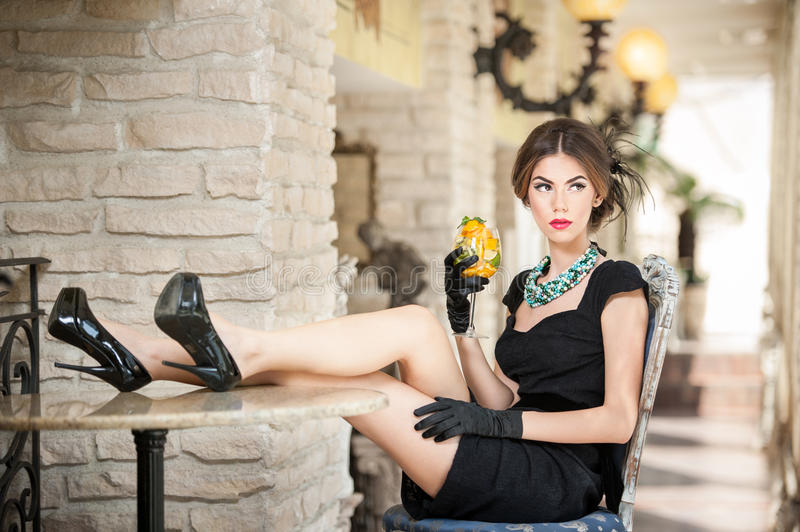 Fashionable attractive young woman in black dress sitting comfortable in restaurant. Brunette relaxing with legs on table. Fashionable attractive young woman in royalty free stock photography
