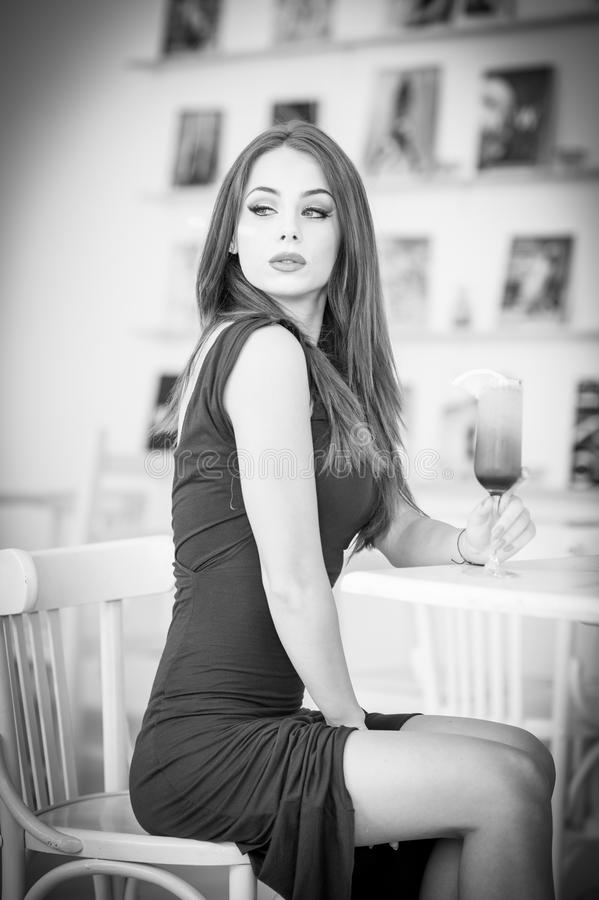 Fashionable attractive young woman in dress sitting in restaurant. Beautiful girl posing in elegant scenery with a juice glass. On the table. Pretty female stock photo