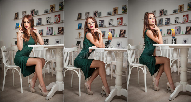 Fashionable attractive young woman in green dress sitting in restaurant. Beautiful redhead posing in elegant scenery with juice. Fashionable attractive young stock image