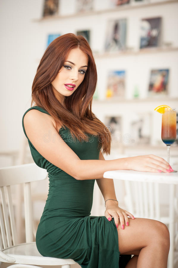 Fashionable attractive young woman in green dress sitting in restaurant. Beautiful redhead posing in elegant scenery with an orange juice glass on the table royalty free stock images
