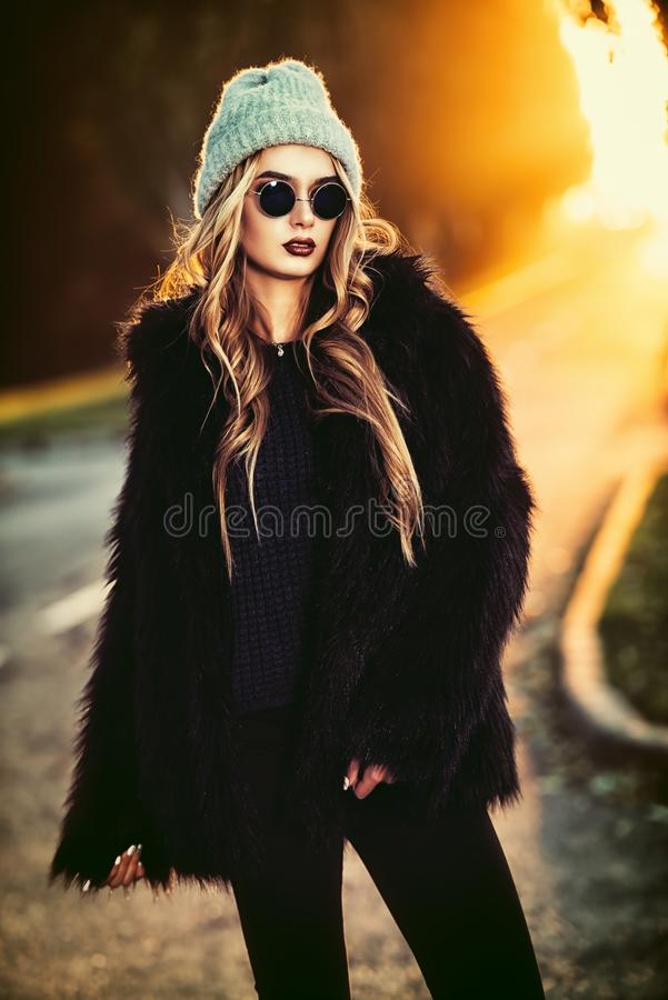Fashionable autumn girl. Autumn fashion shot. Trendy young woman in warm clothes posing on a highway on a sunset. Youth style stock photo