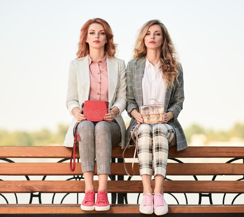 Fall Fashion Outdoor. Woman in Autumn outfit beach. Fashionable autumn women in trendy fall outfit on the bench. Two Gorgeous model girl friends, wavy hair stock photos