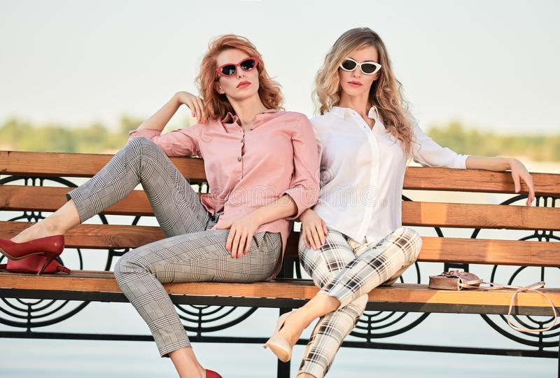 Fall Fashion Outdoor. Woman in Autumn outfit beach. Fashionable autumn women in trendy fall outfit on the bench. Two Gorgeous model girl friends, wavy hair stock image