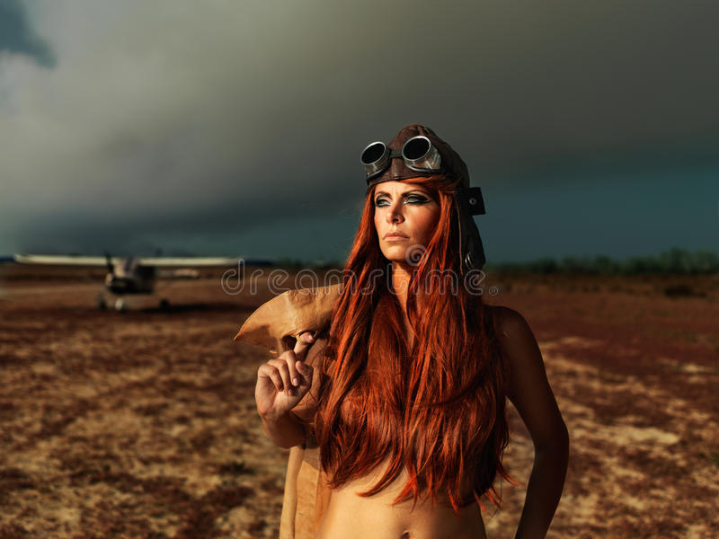 Fashionable aviator woman with smokey plane. Fashion portrait woman aviator outfit smokey sky stock image