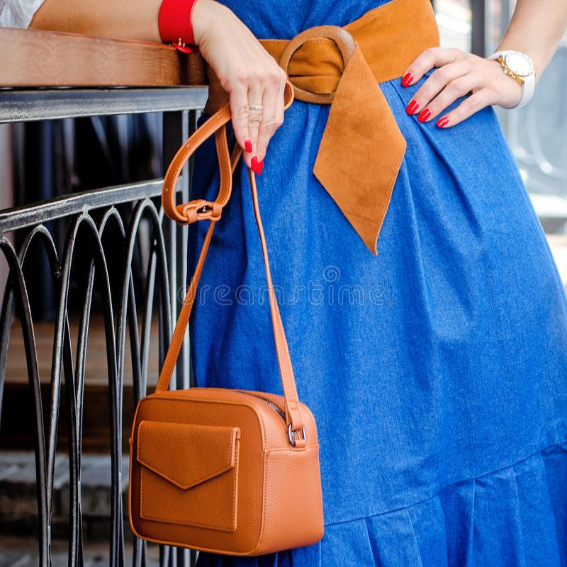 Fashionable bag close-up in female hands.Girl walks in the city outdoors. Stylish modern and feminine image, style. royalty free stock photos