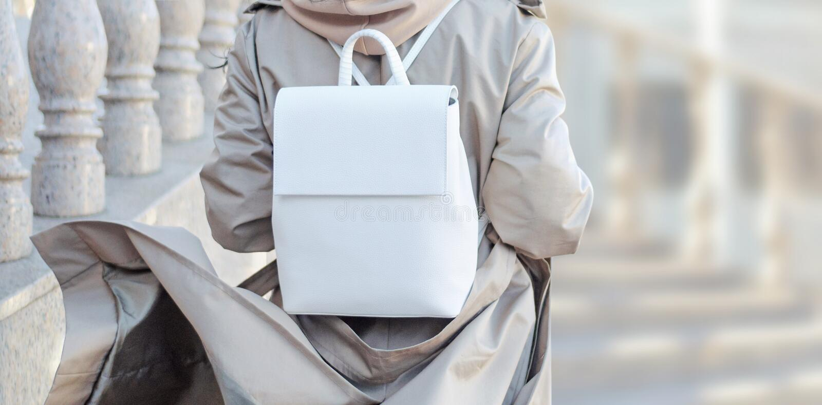 Fashionable bag close-up in female hands.Girl walks in the city outdoors. Stylish modern and feminine image, style. stock image